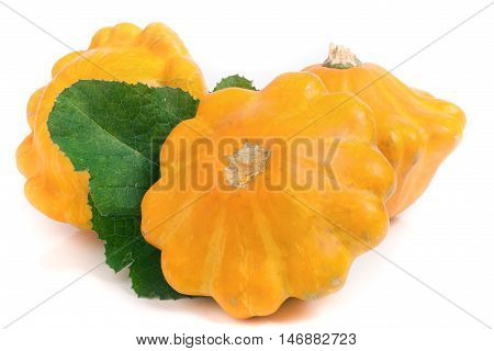 three yellow pattypan squash with leaf isolated on white background.