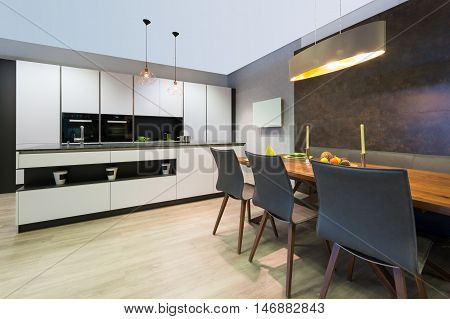 modern elegant white flat kitchen with island and dining table