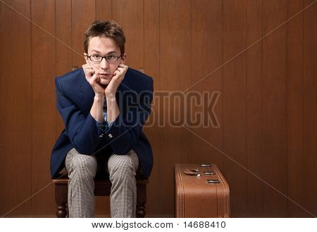 Young Man On Chair With Suitcase
