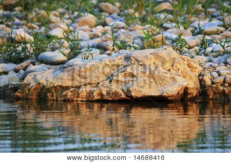 Warm Light On A Rock With Water Reflection