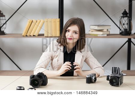 Smiling woman sitting at table with cameras. Attractive brunette looking at camera and holding lens in her hand. Blogger show about photographing