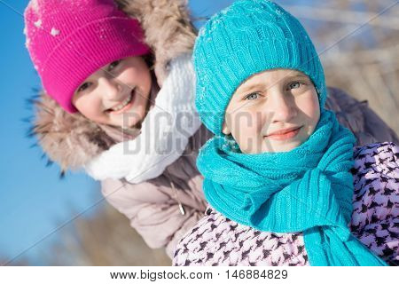 Two cute girls riding sled and having fun