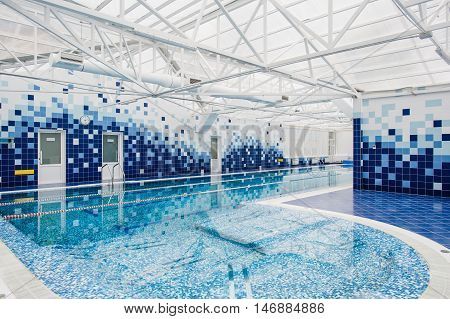 Modern indoor light swimming pool decorated with blue tiles.