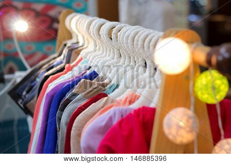 A row of colorful t-shirts, cloth, clothes, pants hanging on hangers