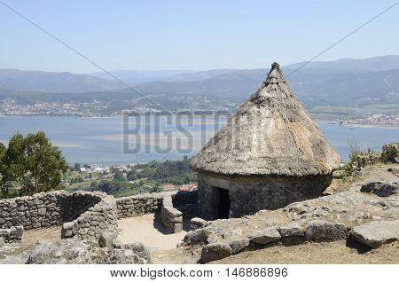 One of the reconstructed houses in the remains of a celtic settlement in Santa Tecla Mount in Galicia Spain with views to the MInho Estuary.