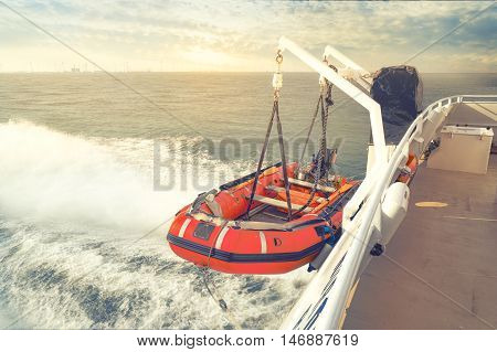 a lifeboat at the back of a boat captured during sunrise