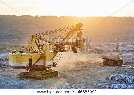Mining. excavator and dump truck in granite or iron opencast