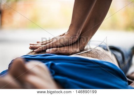 girl making CPR and heart massage to an unconscious man