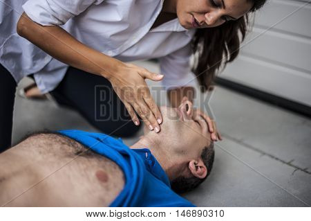 girl checking vital parameters of an unconscious man