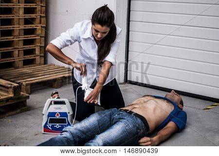 girl applying defibrillator electrode to an unconscious man