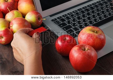Few apple on a computer keyboard and hand with pendrive