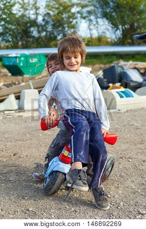 ZAGREB, CROATIA - OCTOBER 21, 2013: Cute little Roma boys sitting on small bike in front of street garbage dump.