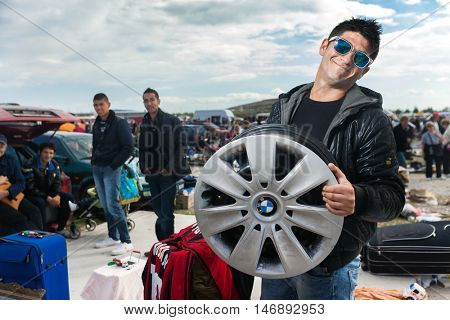 ZAGREB, CROATIA - OCTOBER 20, 2013: Roma salesman holding used car rim at Zagreb's flea market Hrelic.