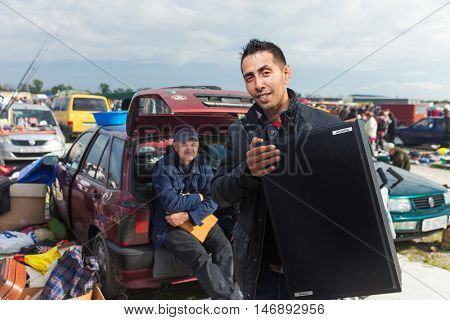 ZAGREB, CROATIA - OCTOBER 20, 2013: Roma salesman holding used speaker at Zagreb's flea market Hrelic.
