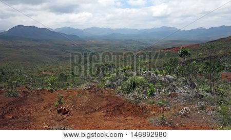 Landscape of New Caledonia, in the wild and natural lands south of the island. Here the land is red and lush vegetation. Photo taken while a hurricane was approaching the island from the north, which explains the presence of a sky with clouds.