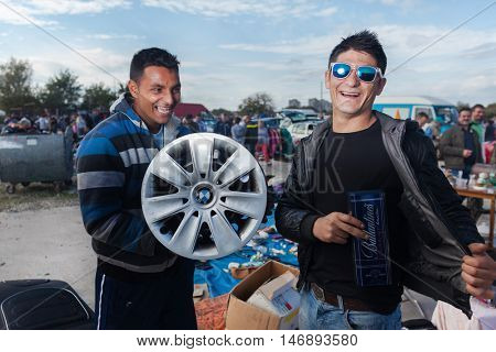ZAGREB, CROATIA - OCTOBER 20, 2013: Roma salesmen holding used car rim and whiskey package at Zagreb's flea market Hrelic.