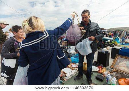 ZAGREB, CROATIA - OCTOBER 20, 2013: Women buying stuff from Roma salesmen at Zagreb's flea market Hrelic.