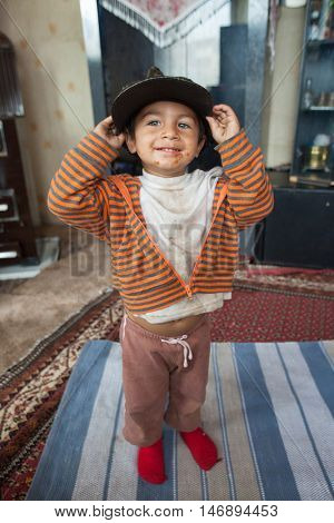 ZAGREB, CROATIA - OCTOBER 21, 2013: Little Roma boy with smudged face holding hat.