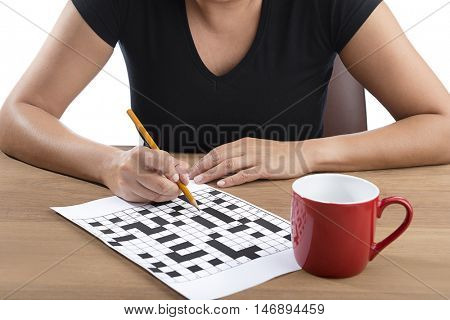 Adult woman solving crossword puzzle with yellow pencil.