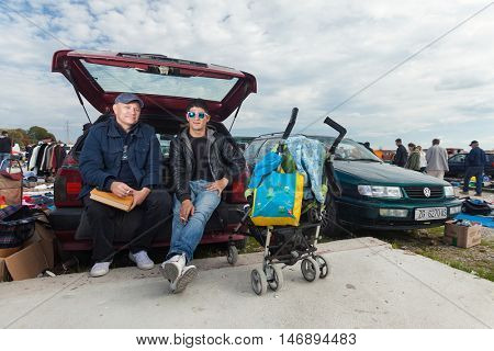 ZAGREB, CROATIA - OCTOBER 20, 2013: Young Roma man sitting at the car trunk with salesman at Zagreb's flea market Hrelic.