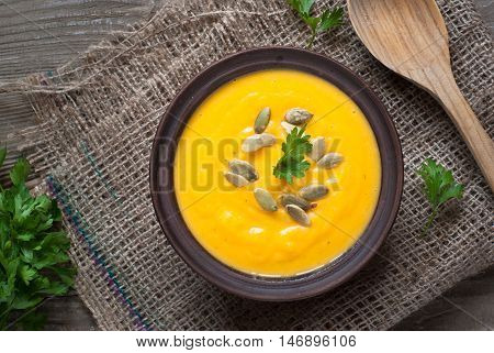 Traditional Pumpkin soup with pumpkin seeds on dark wooden table.