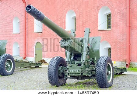 Old army artillery cannon background of fortress wall. Howitzer on wheels. Second  world war.