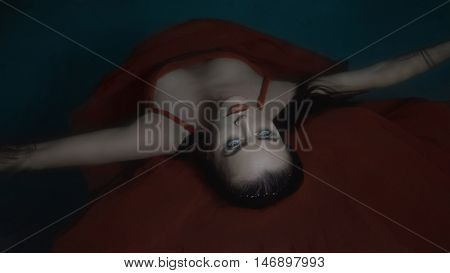 Top view closeup portrait of beautiful mysterious woman looking like a vampire wearing red dress lying on the water at night