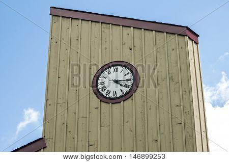Wooden vintage tower clock on blue sky background