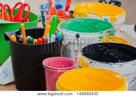 Multi-colored jars with paints, and brush on the table, markers, colors colorful, selective focus