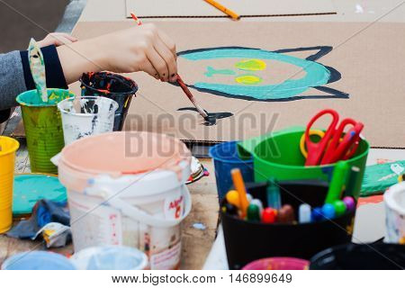Children's creativity. Hand drawing a child paints. Cans of paint on the table, selective focus