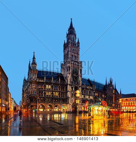 Marienplatz at night with Town Hall of Munich Germany and other buildings - cafes bars shops and restaurants. Reflection after the rain
