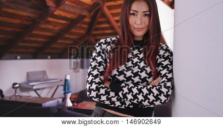 Japanese woman leaning against wall wearing knitted sweater. Happy and comfy.
