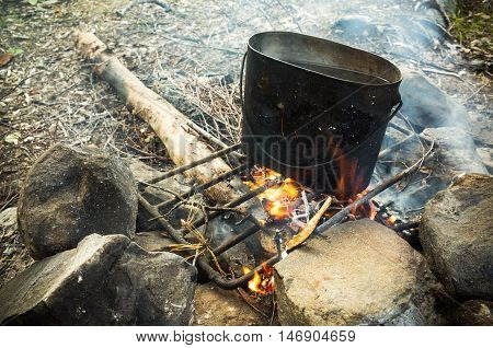 Old Black Pan With Boiling Water On Bonfire