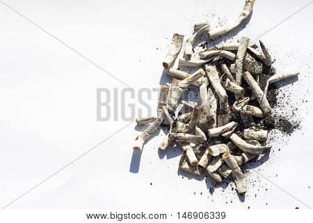 Cigarette butt isolated on white. Top view with copy space