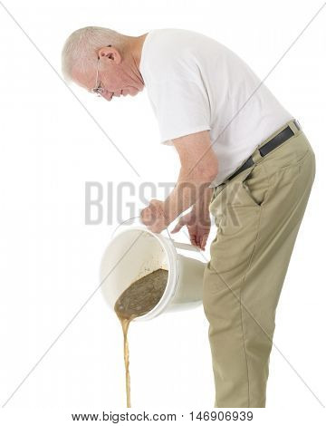 A senior man dumping filthy water from a white, plastic bucket.  On a white background.