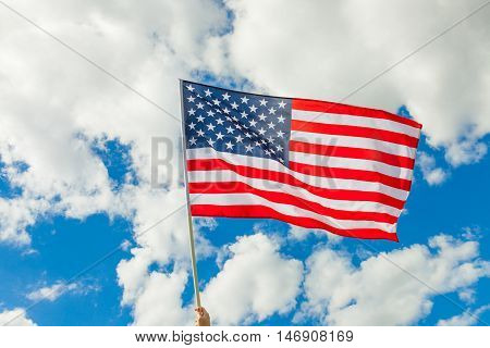 USA flag on flagpole with clouds on the background