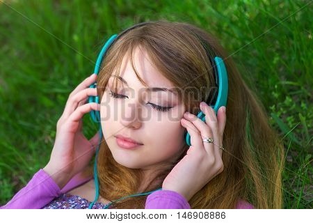 Beautiful girl lying on the grass and listening music with headphones at the park