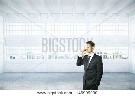 Businessman talking on phone in empty light hangar interior with daylight and city view. 3D Rendering
