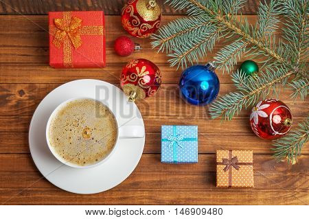 Little coorful gift boxes christmas toys branch fir-tree and cup of coffee on wooden background.