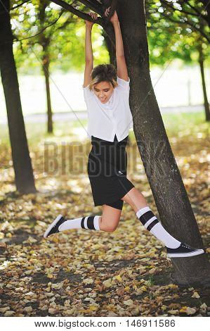 attractive young woman hanging on a tree branch, laughing, swinging his feet in autumn park.