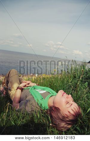 Young beautiful girl lying with her eyes closed and a smile on his face on the green grass on the bay on a warm sunny day