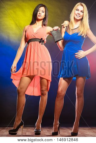Feminism and emacipation. Party celabration carnival. Two attractive dancing women in dresses on colorful background in studio.