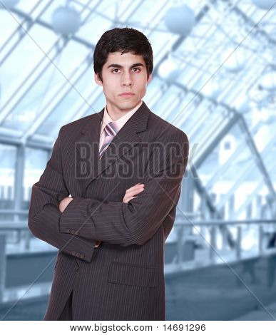 Closeup of a young smiling business man standing in a light and mordern business hall.