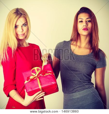 Gifts giving for any occasion. Two young ladies with red gift. Blond girl has nice dress and mulatto lady wears grey outfit. Both are very beautiful.