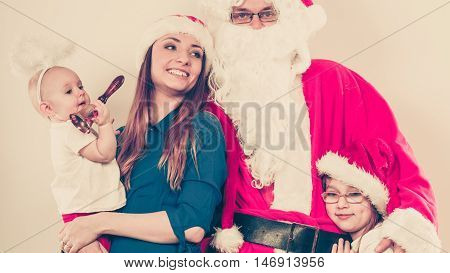 People christmas time household concept. Happy family together with Santa Claus. Portrait of mother daughters and Christmas Father.