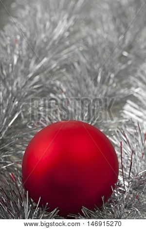 closeup of a red christmas ball on silver tinsel