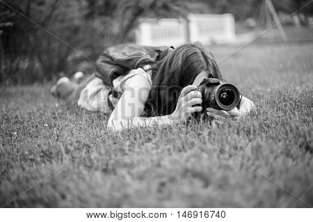 Photographer for the photoshoot. Photography as a lifestyle. Passionate keen about photographing creative people. The photographer is in the grass for a perspective shot.