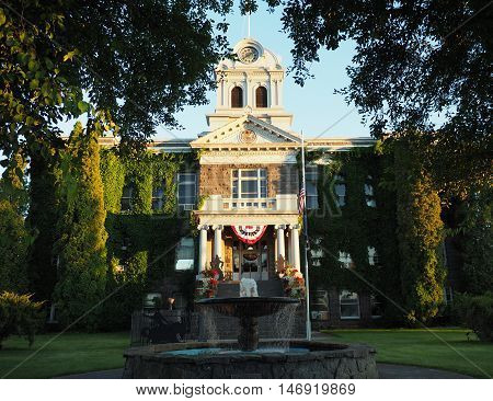 The Crook County Courthouse in Prineville in Central Oregon with its beautiful fountain flags and flame stands in the golden light of the retreating sun on a summer day.