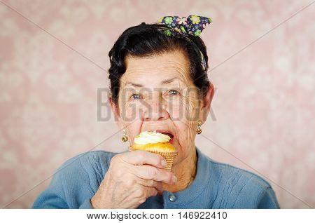 Older hispanic happy woman wearing blue sweater sitting in front of camera having a bite off cupcake.