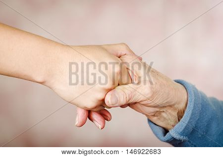 Closeup of two hands holding each other apeearing to be that of a young and one old person.